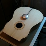 Testing the vibration of the guitar top with a vibration-transmiting speaker